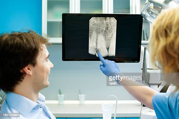 Dentist Professional Explaining  X-Ray Image to Patient