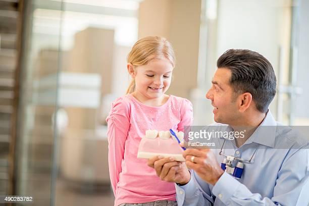 Dentista mostrando una bambina come spazzola i denti