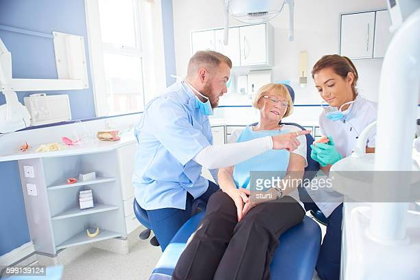 dentist showing senior patient model of dentures
