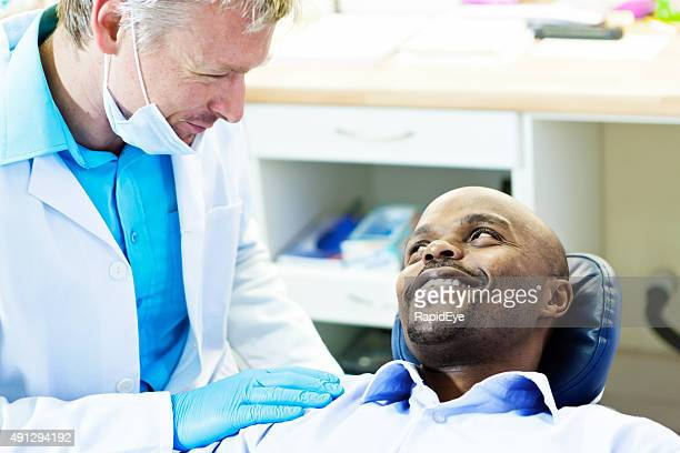 Dentist talking to smiling male patient in dental chair
