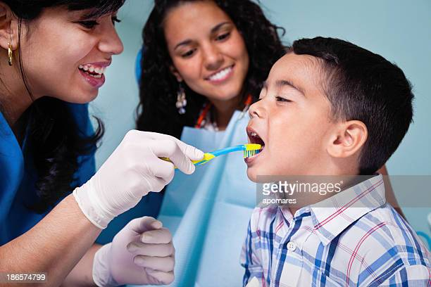 Dentist teaching toothbrush use to child patient