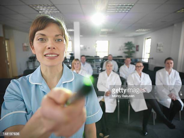 Dentist using screen in lecture theatre with apprentice dentists