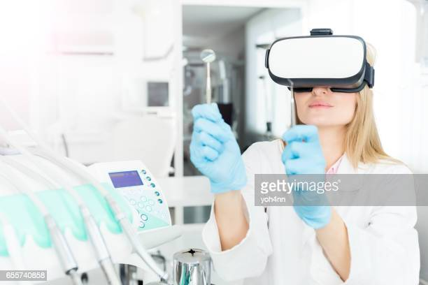 Dentist using virtual reality headset and holding tools