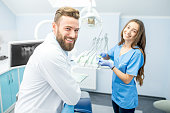 Handsome dentist with young female assistant in uniform prepairing for the job at the dental office