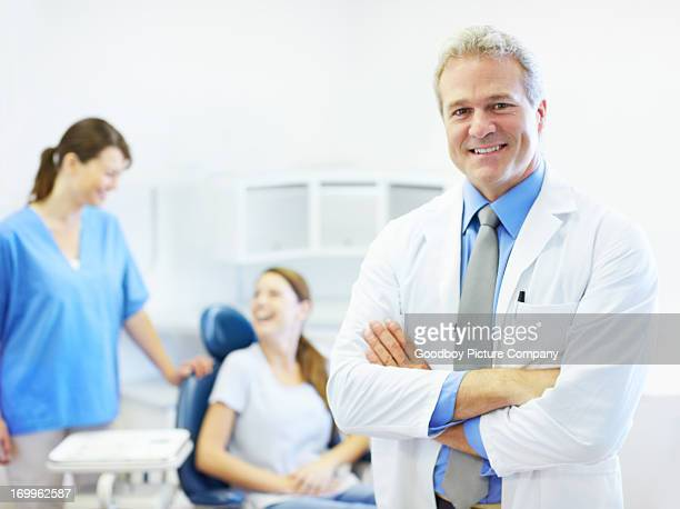 Dentist with patient and staff in background