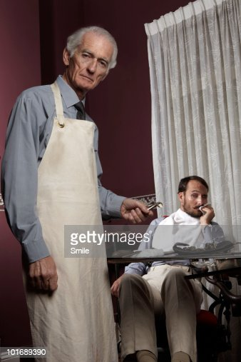 Dentist with pulled tooth, patient in pain : Stock Photo