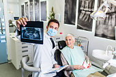 Handsome male dentist checking x-ray image or scan while beautiful senior woman receiving a dental treatment.