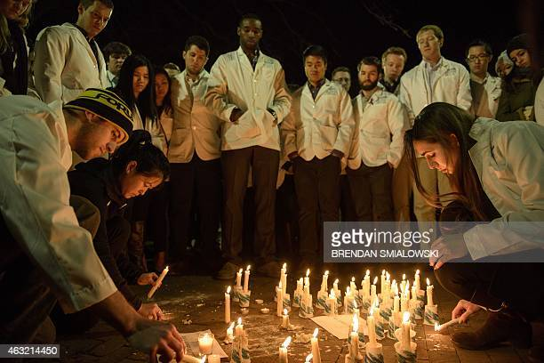 Dentistry students and others watch as a makeshift memorial is made during a vigil at the University of North Carolina following the murders of three...