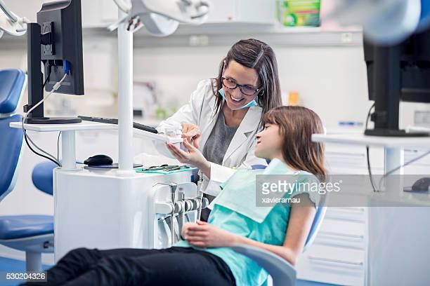 Assistant de dentiste montrant les dents modèle pour femme
