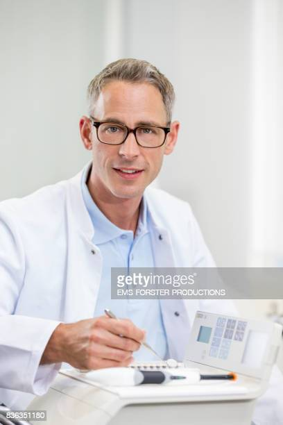 Dentist's office - mid adult dentist with short greying hair and a toothy smile in blue polo shirt and white medical worker wear