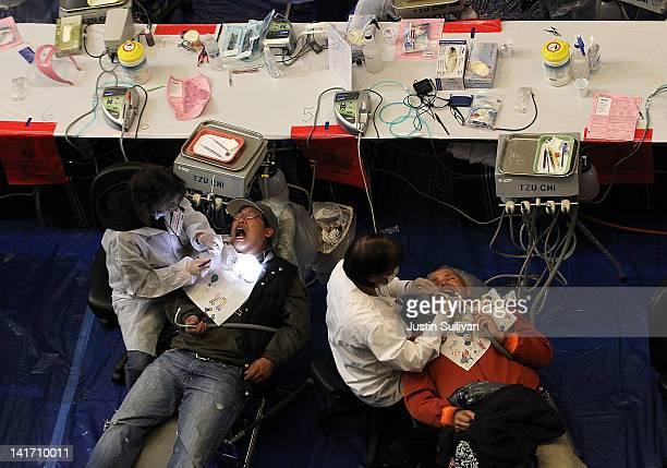 Dentists perform dental procedures during the Remote Area Medical free clinic at the Oco Coliseum on March 22 2012 in Oakland California Thousands of...