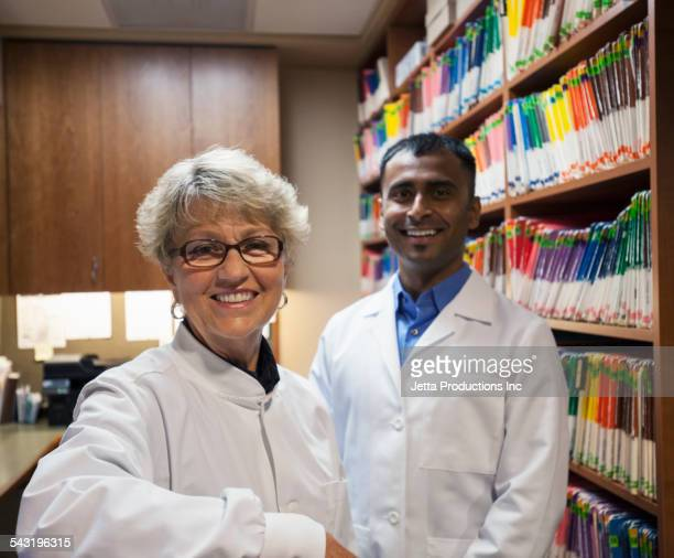 Dentists smiling near wall of medical files