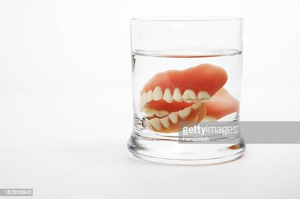 Dentadura postiza en un vaso de agua