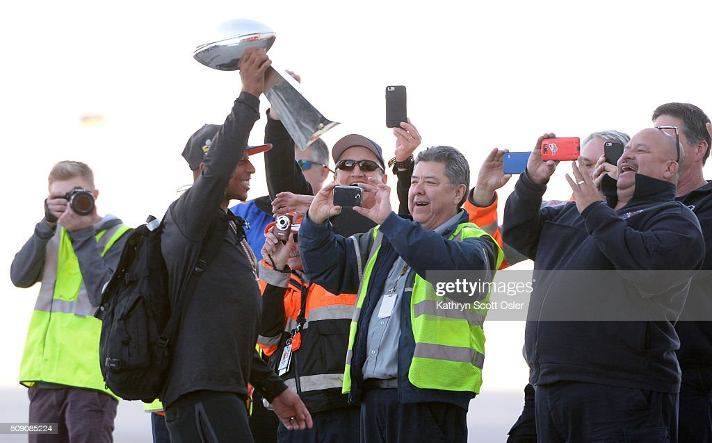 Denver airport crews cheer and take photos of Chris Harris as he passes by holding the Vince Lombardi Tophy after members of the Denver Broncos football team arrive home at Denver international Airport on Monday, Feb. 8, 2016.