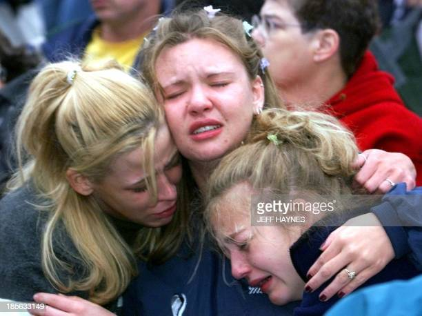 Denver area high school students Rhianna Cheek Mandi Annibel and Rachel Roof comfort one another 21 April 1999 during a candle light vigil at Civic...