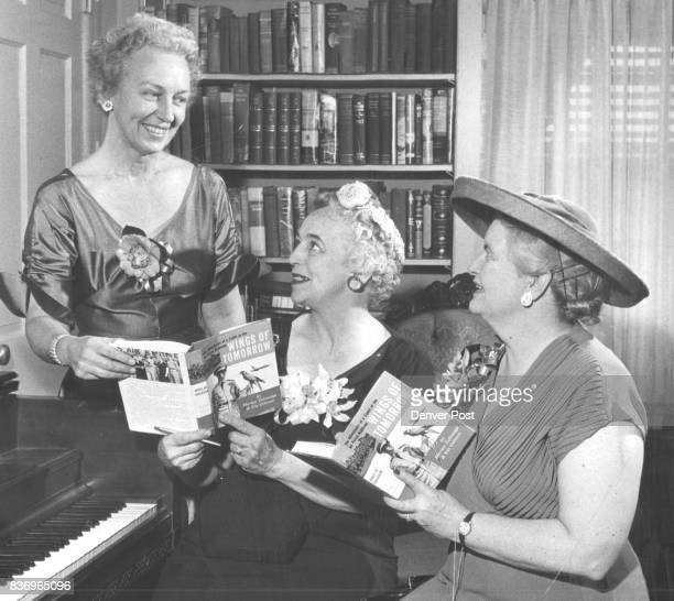 Denver authors Mrs Marian Huxoll Talmadge right and Mrs Iris Pavey Gilmore center autograph advance copies of their book about Air Force Academy life...