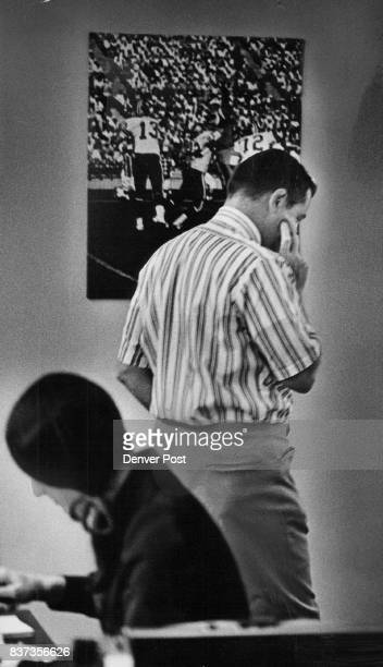 Denver Bronco coach and general manager John Ralston stands pondering draft under picture of former Bronco quarterback Steve Tensi throwing forward...