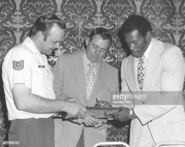 Denver Bronco running back Floyd Little right and Bronco Coach John Ralston give autographs to M Sgf John R Olson at a recent meeting of the Aurora...