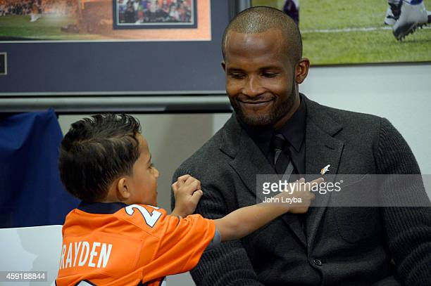 Denver Broncos Champ Bailey son Brayden points at his Broncos lapel pin on his jacket during a press conference to announce his retirement as a...