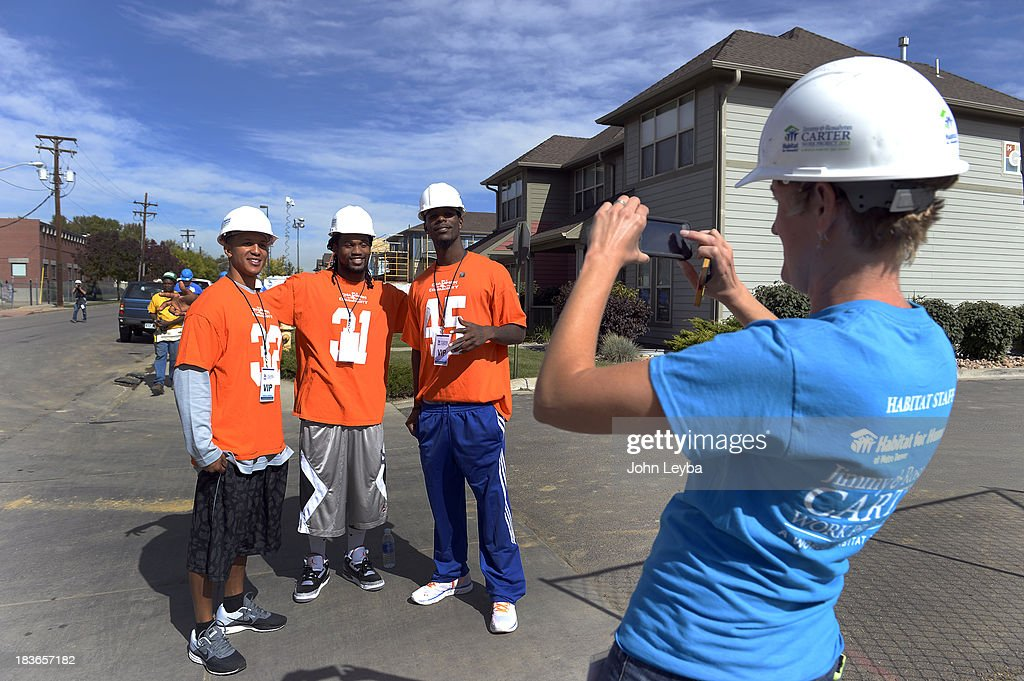 Denver Broncos defensive back Tony Carter (32) Denver Broncos cornerback Omar Bolden (31) and Denver Broncos cornerback Dominique Rodgers-Cromartie (45) pose for a photo for Heather Lafferty, Habitat Metro Denver CEO, as players join together to pay a visit to 30th annual Jimmy & Rosalynn Carter Work Project October 9, 2013 at the Globeville project.