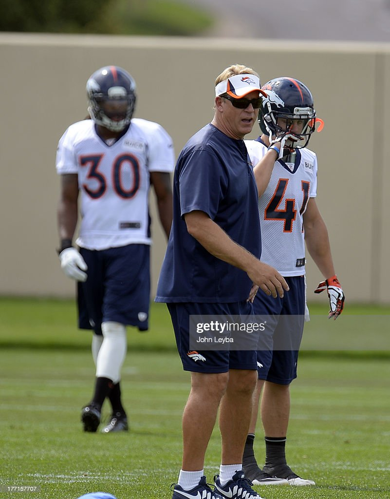 Denver Broncos defensive coordinator works with the defense during practice August 22, 2013 at Dove Valley
