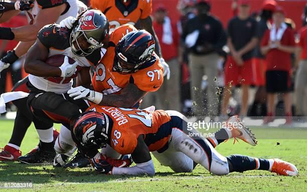 Denver Broncos defensive tackle Billy Winn and Denver Broncos outside linebacker Shaquil Barrett put a hit on Tampa Bay Buccaneers running back...