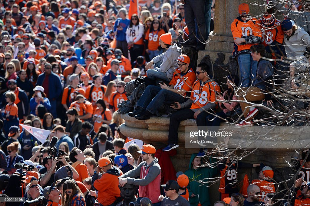 Denver Broncos fans get a good vantage point from a statue at Colfax and Broadway during the Denver Broncos Super Bowl 50 celebration parade February 07, 2016.