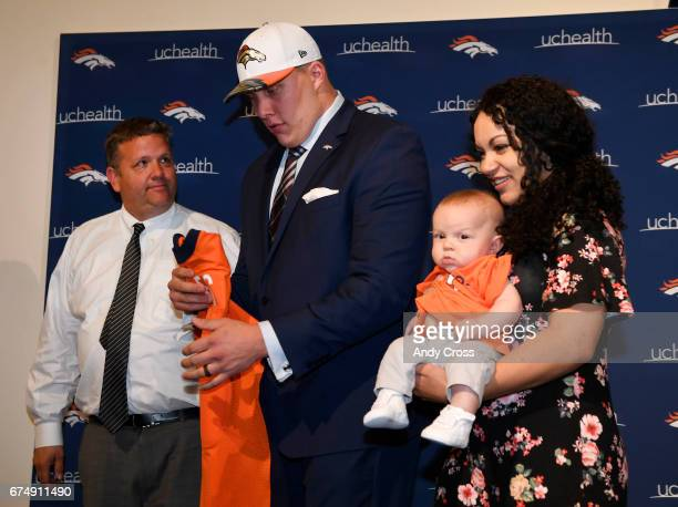 Denver Broncos first round draft pick Garett Bolles folds up his new Broncos jersey as guardian Greg Freeman left and his wife Natalie and their son...