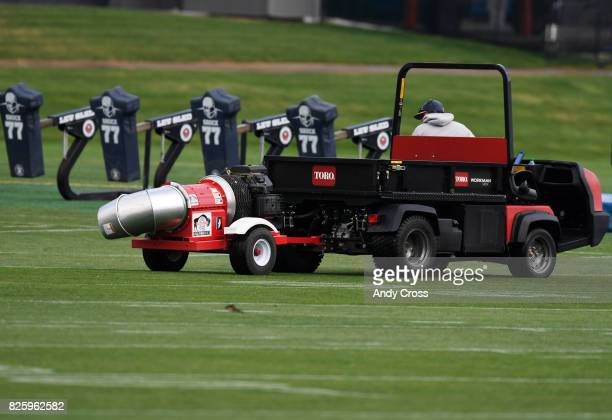 Denver Broncos grounds crew member pulls a gas powered dryer to help dry off the practice fields at Dove Valley after a heavy overnight rainstorm...