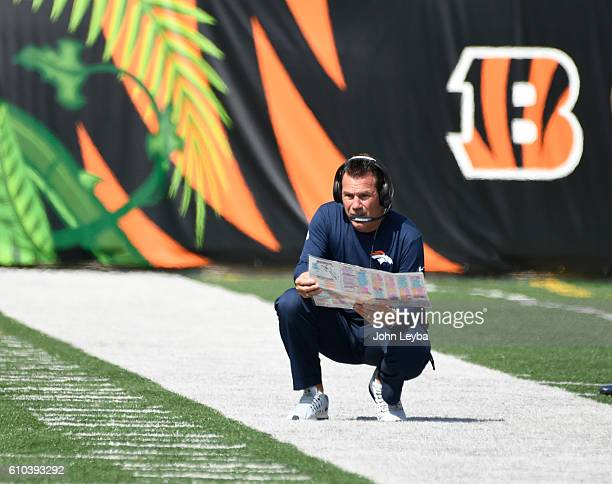 Denver Broncos head coach Gary Kubiak kneels looking at the play chart during the first quarter agains the Cincinnati Bengals September 25 2016 at...