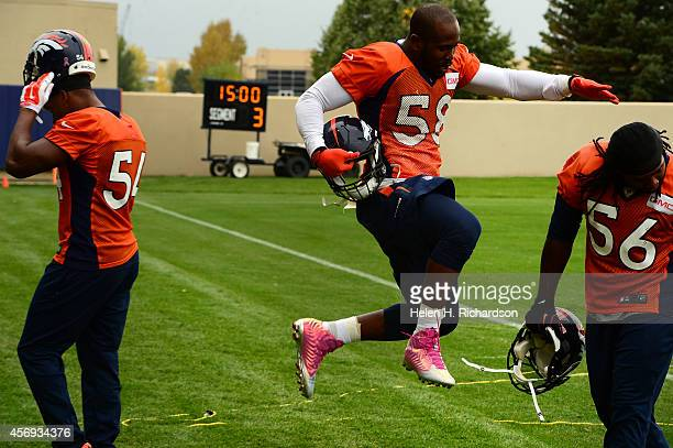 Denver Broncos linebacker Von Miller #58 plays around with linebacker Nate Irving #56 as they leave the field after at Dove Valley in Englewood CO on...