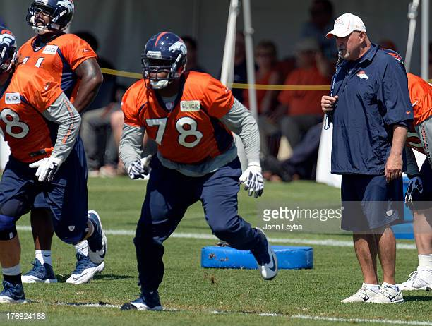 Denver Broncos offensive line coach Dave Magazu watches Denver Broncos tackle Ryan Clady run through drills during practice August 19 2013 at Dove...