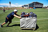 Denver Broncos operations assistants wheels in the helmets after practice on day 12 of training camp August 12 2015 at Broncos headquarters