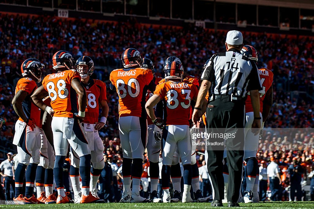 Denver Broncos players huddle around Peyton Manning #18 during a game against the Washington Redskins at Sports Authority Field Field at Mile High on October 27, 2013 in Denver, Colorado.