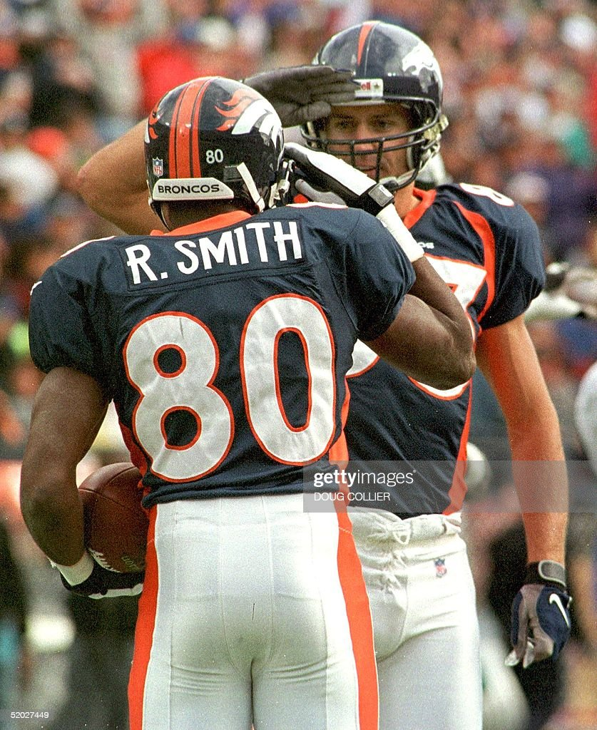 92a0cfb44e1 ... Jersey Denver Broncos players Rod Smith (L) and Justin Armour (R) give  each ...
