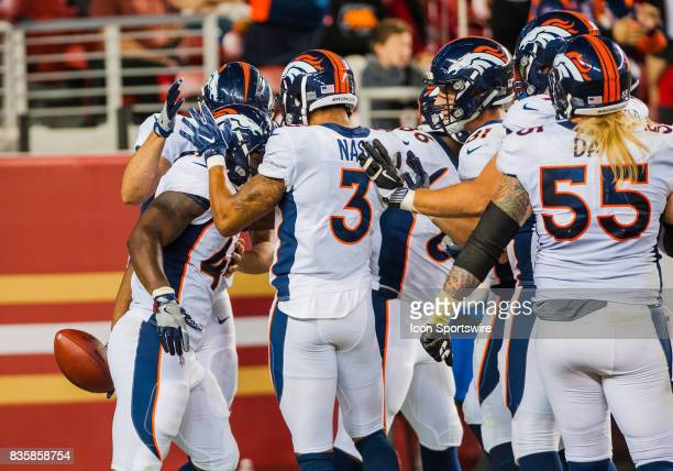 Denver Broncos players swarm Denver Broncos running back Juwan Thompson after scoring a touchdown during the preseason game between San Francisco...