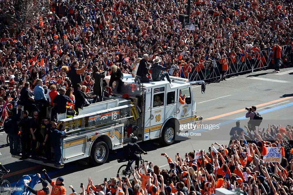 Denver Broncos QB Peyton Manning (dark vest, orange sleeves) rides on top of Denver Fire engine #18 along with Von Miller and John Elway and many others during the Denver Broncos Super Bowl 50 celebration parade February 07, 2016.