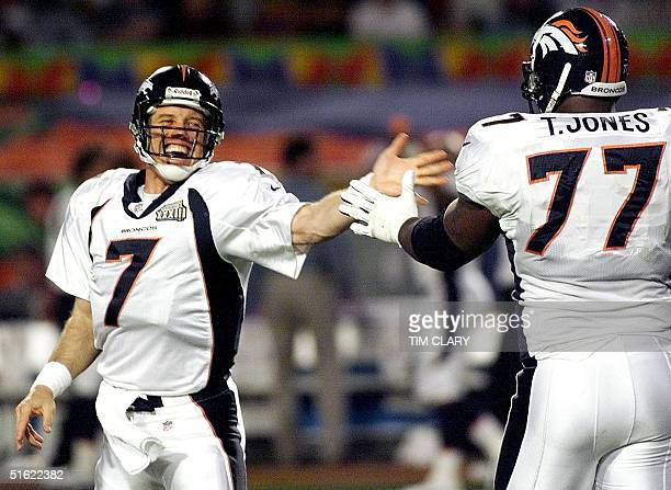 Denver Broncos quarterback John Eway slaps hands with tackle Tony Jones after the Broncos scored on an 80yard touchdown pass play in first half...