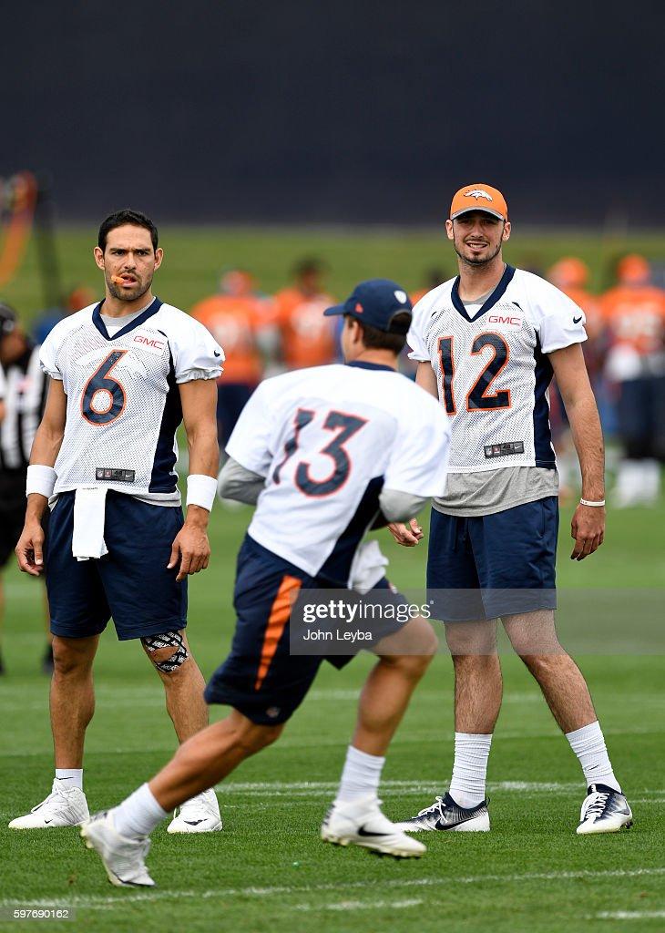 Denver Broncos quarterback Mark Sanchez and Denver Broncos quarterback Paxton Lynch watch Denver Broncos quarterback Trevor Siemian run through...