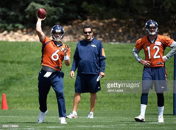 Denver Broncos quarterback Mark Sanchez throws a pass as quarterbacks coach Greg Knapp and QB Paxton Lynch look on during OTA's May 31 2016 at...