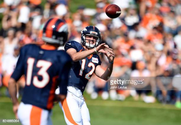 Denver Broncos quarterback Paxton Lynch catches a pass from quarterback Trevor Siemian in throwing drills during training camp on July 31 2017 in...