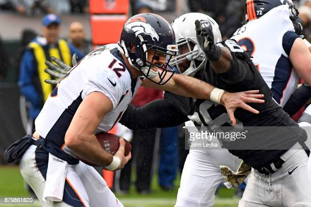 Denver Broncos quarterback Paxton Lynch gets sacked by Oakland Raiders defensive end Denico Autry during the second quarter on November 26 2017 in...