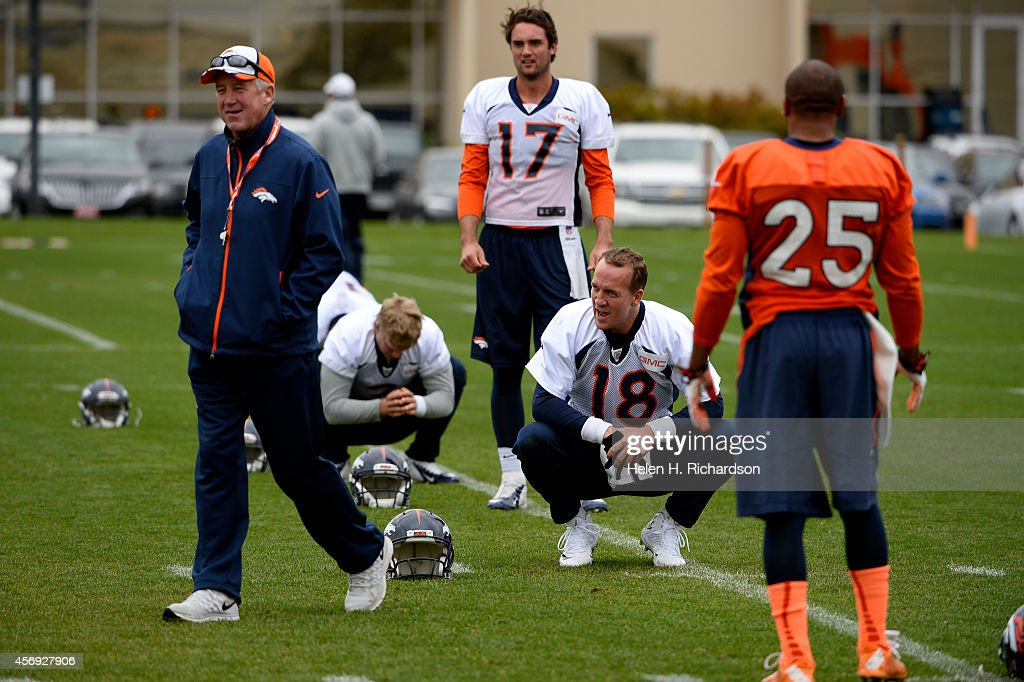 Denver Broncos quarterback <a gi-track='captionPersonalityLinkClicked' href=/galleries/search?phrase=Peyton+Manning&family=editorial&specificpeople=184524 ng-click='$event.stopPropagation()'>Peyton Manning</a>, #18, says something that makes coach <a gi-track='captionPersonalityLinkClicked' href=/galleries/search?phrase=John+Fox+-+Coach&family=editorial&specificpeople=206657 ng-click='$event.stopPropagation()'>John Fox</a> smile as Manning, back up quarterback <a gi-track='captionPersonalityLinkClicked' href=/galleries/search?phrase=Brock+Osweiler&family=editorial&specificpeople=6501030 ng-click='$event.stopPropagation()'>Brock Osweiler</a>, #17, and cornerback Chris Harris Jr. # 25, right, in orange, warm up before daily practice at Dove Valley in Englewood, CO on October 9, 2014.