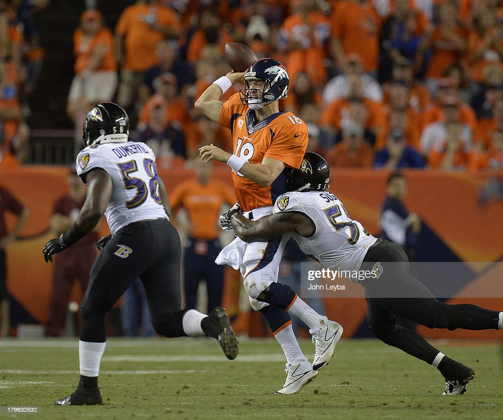 Denver Broncos quarterback Peyton Manning (18) is wrapped up by Baltimore Ravens outside linebacker Terrell Suggs (55) in the third quarter. The Denver Broncos took on the Baltimore Ravens in the first game of the 2013 season at Sports Authority Field at Mile High in Denver on September 5, 2013.