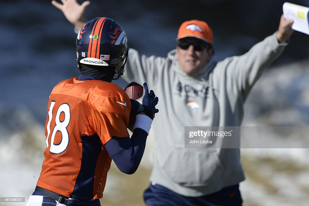 Denver Broncos quarterback Peyton Manning (18) runs through drills as Gregg Knapp ttys to distract him during his throwing motion at practice January 8, 2014 at Dove Valley. The Denver Broncos are preparing for their Divisional Game against the San Diego Chargers at Sports Authority Field.