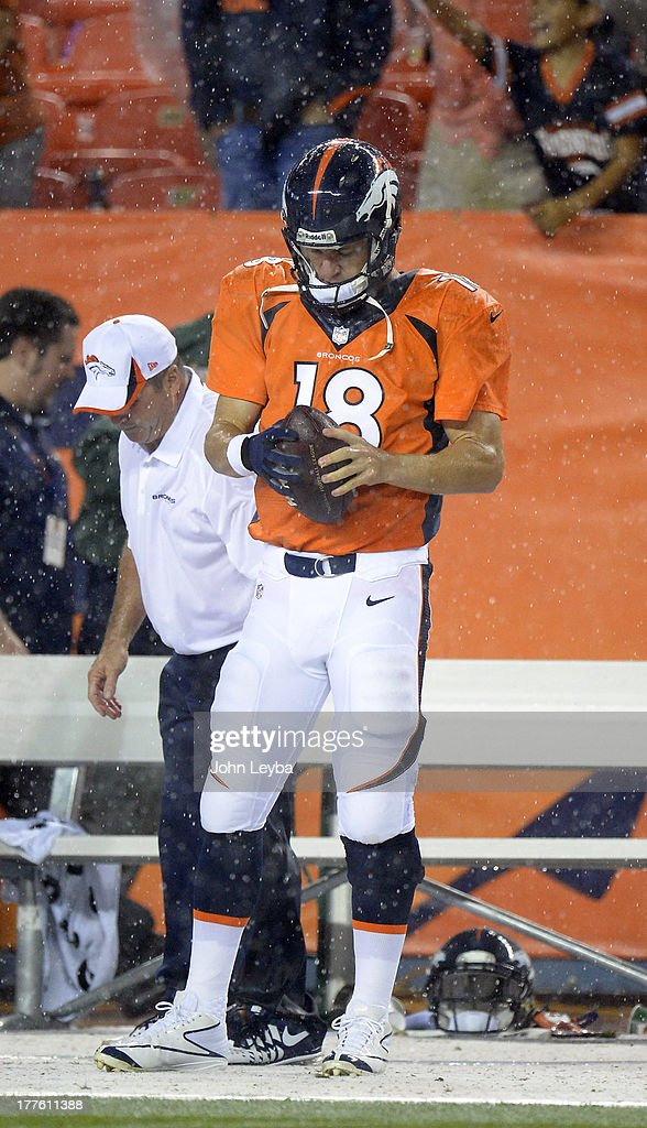 Denver Broncos quarterback Peyton Manning (18) test out the glove on his throwing hand when the rain came down in the fourth quarter against the St. Louis Rams August 24, 2013 at Sports Authority Field at Mile High.