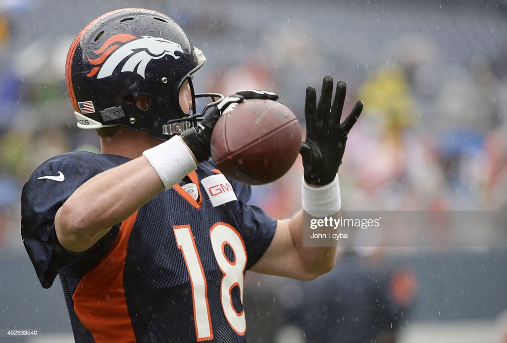 Denver Broncos quarterback Peyton Manning (18) throws a pass as he wears the glove during a rain day on day six of the Denver Broncos 2014 training camp July 30, 2014 at Sports Authority Field at Mile High Stadium.