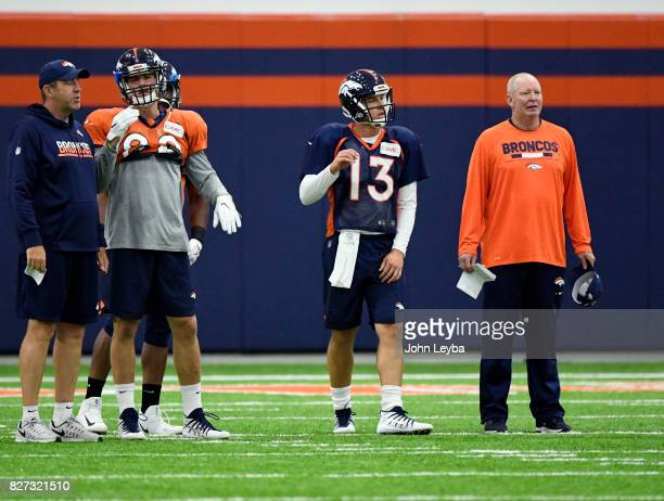 Denver Broncos quarterback Trevor Siemian and quarterbacks coach Bill Musgrave look on during practice The team moved practice indoors during...