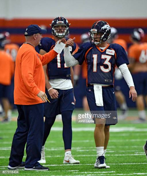 Denver Broncos quarterback Trevor Siemian chats with quarterbacks coach Bill Musgrave during practice with quarterback Paxton Lynch in the back...