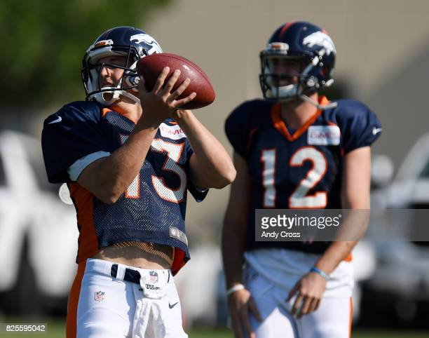 Denver Broncos quarterback Trevor Siemian makes a catch as quarterback Paxton Lynch awaits a throw during training camp at Dove Valley August 02 2017